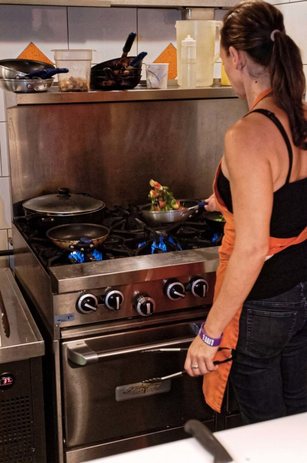 woman frying vegetables in a pan
