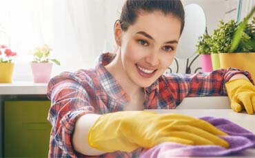 woman wiping furniture dust